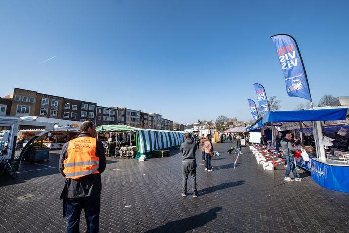 Met onder meer afzetlinten zorgen kraamhouders ervoor dat bezoekers van de Nijmeegse markt voldoende 'corona-afstand' van elkaar houden.