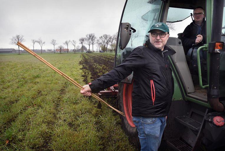 Een vrijwilliger van de vogelbescherming loopt donderdag in de Binnenveldse Hooilanden voor een boer it en zet stokken bij gevonden nesten. De boer werkt daar omheen. Beeld null