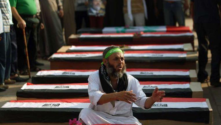 Een aanhanger van de afgezette president Morsi naast een lege kist tijdens een nep-begrafenis van de slachtoffers van een schietpartij dinsdag. Beeld afp