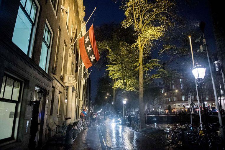 De vlag hangt halfstok op de ambtswoning. Voor de woning liggen bloemen en kaartjes Beeld anp