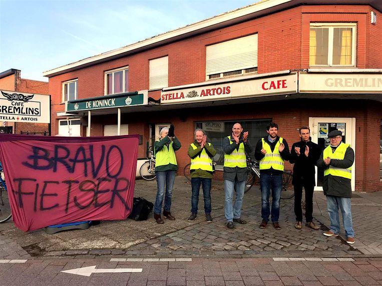 Enkele sympathisanten applaudisseren samen met schepen van Ruimtelijke Ordening Marc De Cordt (Groen) voor voorbijrijdende fietsers.