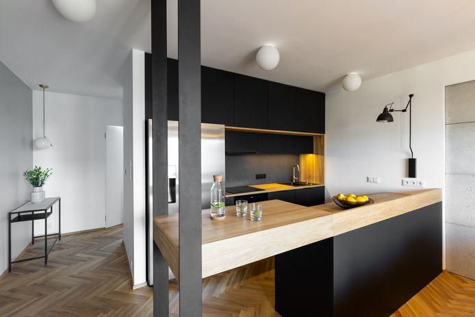 Modern huis: veel zwart en een houten vloer in visgraatpatroon.