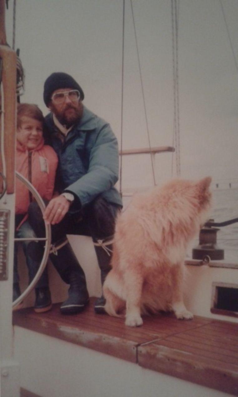 Leo van Hooft op zijn zelfgebouwde zeilschip met zoontje Paul van vijf jaar en hond Suzy. Beeld PRIVEFOTO