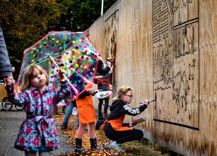 Kinderen kleuren op een schutting de historie van het Rijtven