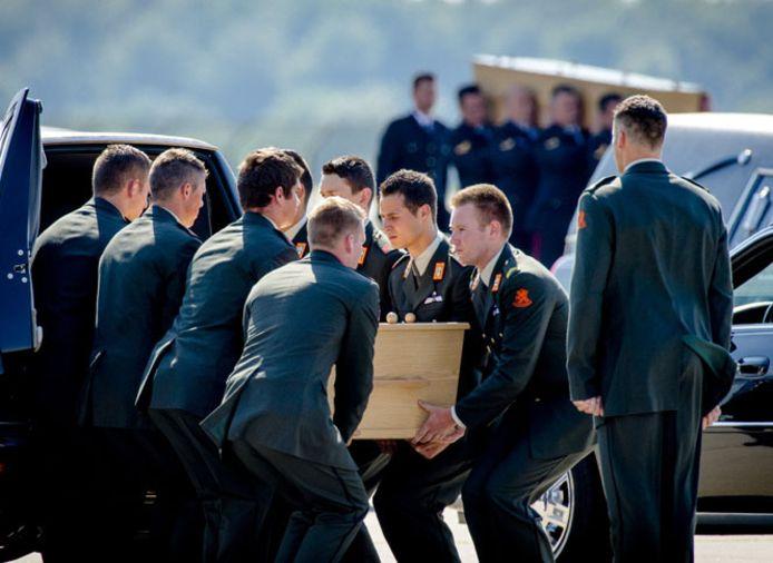 Militairen dragen op vliegbasis Eindhoven kisten met daarin de lichamen van slachtoffers van de vliegramp in Oekraïne.