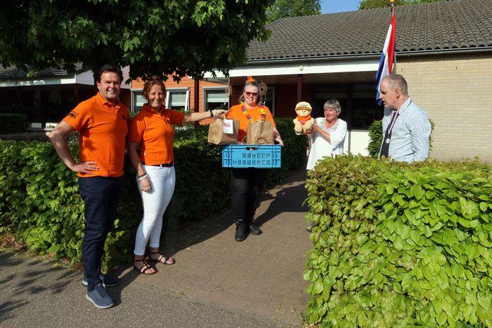 Kristel en Ivo Gijsbers overhandigen de maaltijden namens de Oranjemarkt aan Claudia Slokker van Severinus (midden). Op de foto staan ook de bewoners Ciska en Johan.
