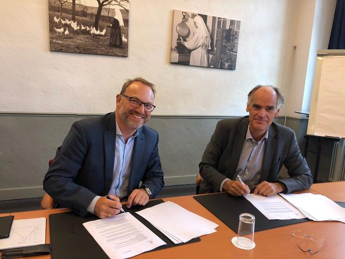 Algemeen directeur Geert van den Enden van Bernhoven (links) en Leon van Halder van het Radboudumc tekenen de samenwerkingsovereenkomst.