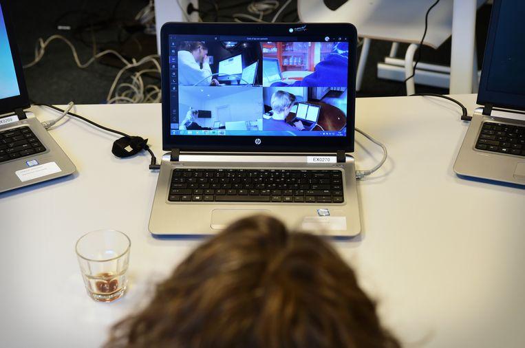 Leerlingen van het Luzac doen schoolexamen dat online wordt afgenomen. Leraren surveilleren door het in de gaten houden van het laptopscherm waarop de leerlingen te zien zijn die aan hun examen werken.  Beeld Marcel van den Bergh / de Volkskrant