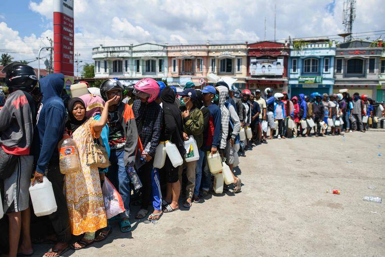 Overlevenden in de rij voor benzine in Palu. Beeld AFP