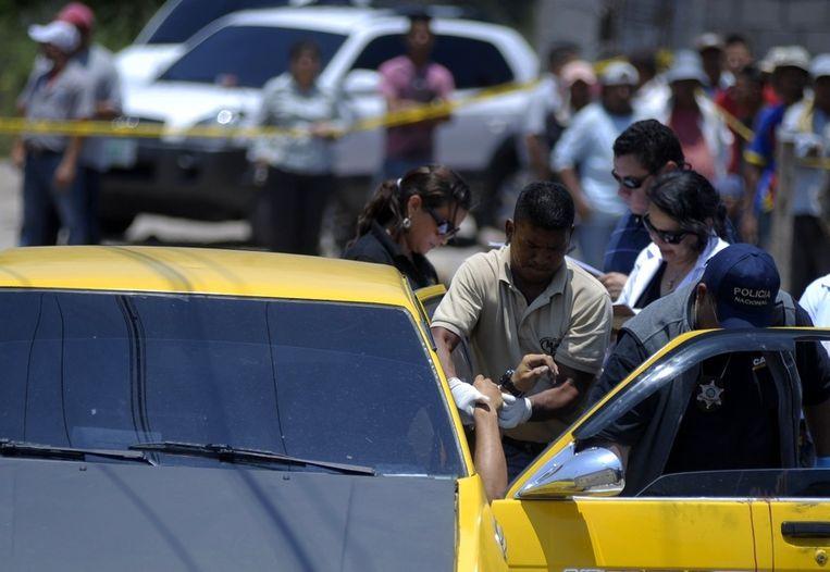 Politieagenten bij de auto waarin maandag de drie mannen werden gedood. Beeld reuters