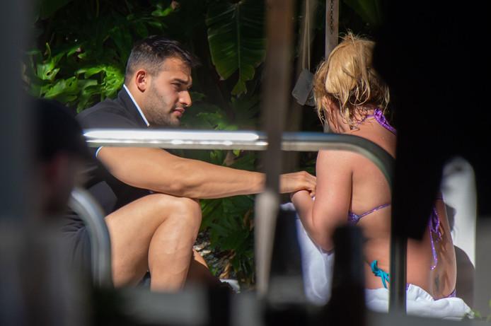 Sam Asghari et Britney Spears discutant au bord de la piscine.