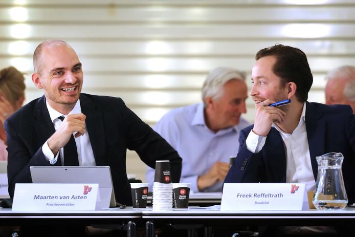 Twee fractieleden van coalitiepartij VVD met op de achtergrond oppositieleider Hans Smolders.
