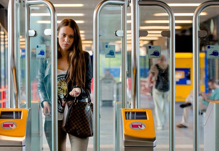 en reiziger loopt door een toegangspoortje op het station in Woerden. Beeld Anp