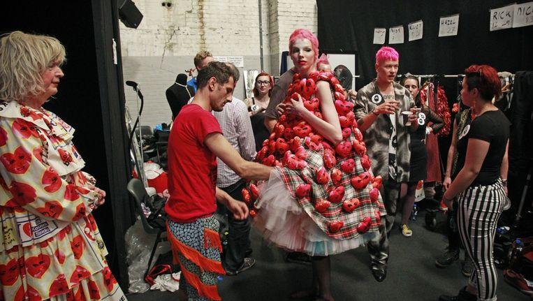 Bas Kosters en zijn modellen vlak voor zijn show tijdens de vorige Amsterdam Fashion Week in juli; links 'ladyspeaker' Margreet Dolman. Beeld Ade Johnson/ANP KIPPA