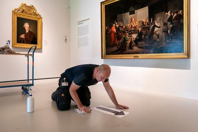 Riny van den Heuvel van het bedrijf Tars plakt een sticker die de looplijn bepaalt in de expositie Meesterwerken uit Wenen. Foto Marc Bolsius