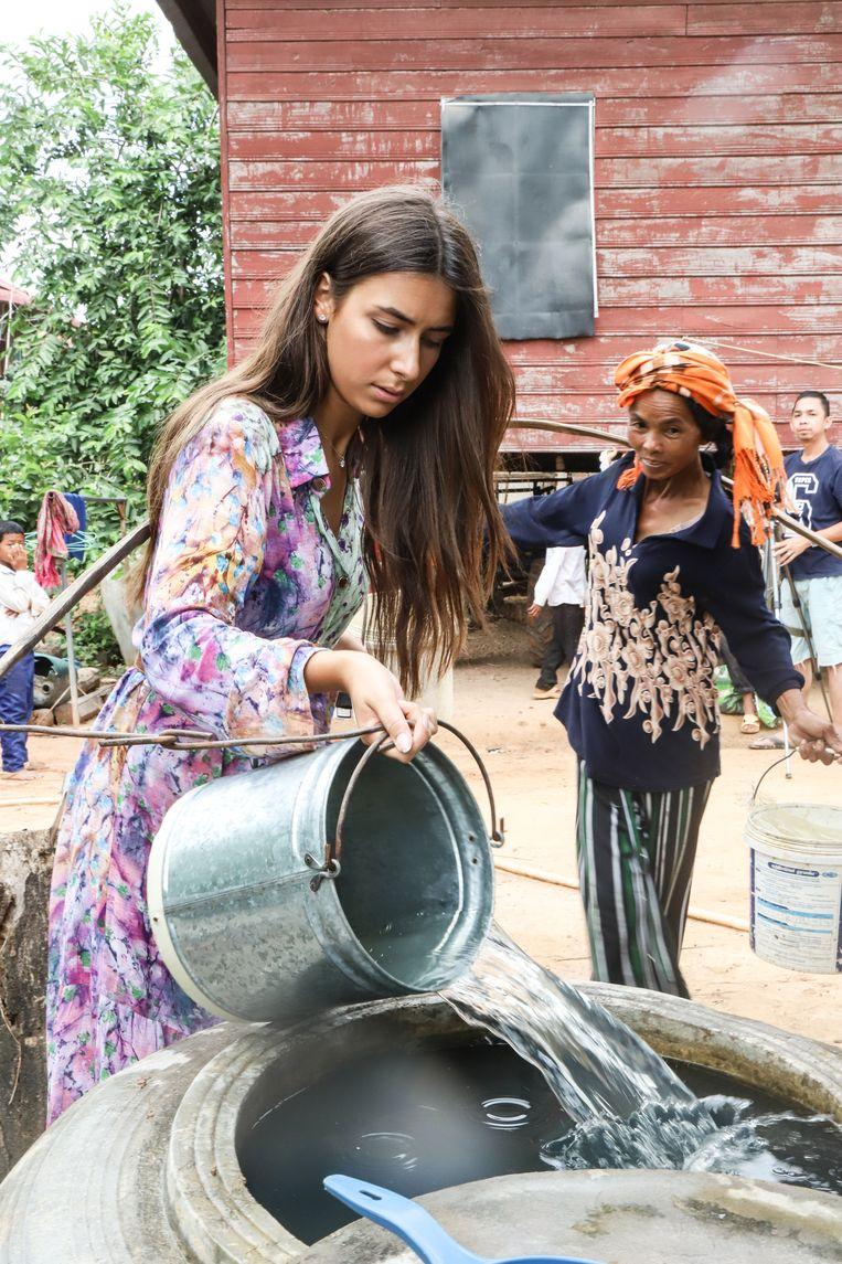 Elena laat zien hoe de bidon waarmee water gehaald wordt uitgewassen moet worden.
