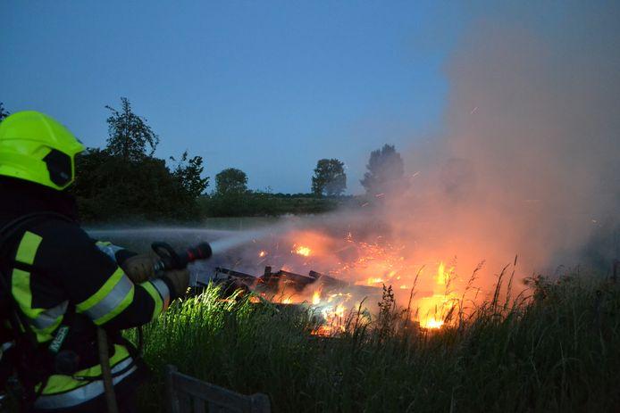 De brandweer blust het vuurt aan de Schansedijk.