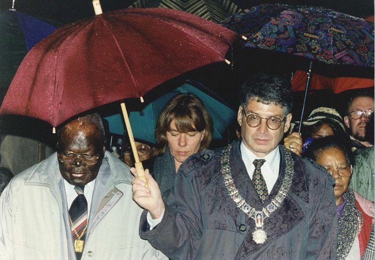 Burgemeester Ed van Thijn houdt tijdens de eerste herdenking van de Bijlmerramp een paraplu boven Pa Sem. Beeld anp