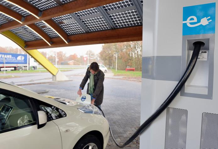 Een automobilist laadt zijn elektrische auto op bij een snellaadstation langs de A1.