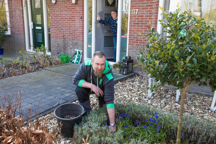 Hovenier Robin van Domselaar in de tuin aan het werk. Zijn bedrijf houdt gratis tuinen bij van zorgpersoneel in de wijk