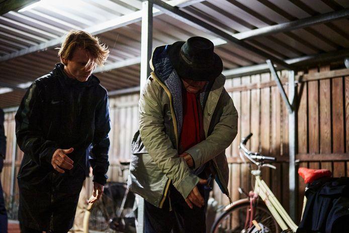Sheltersuit-oprichter Bas Timmer legt sheltersuit uit aan dakloze Gerard.