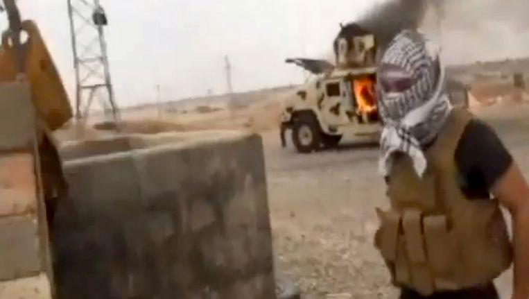 Een strijder van ISIS staat voor een uitgebrande auto in Tikrit, de olierijke stad die de terreurgroep na Mosul in handen heeft gekregen. Beeld null