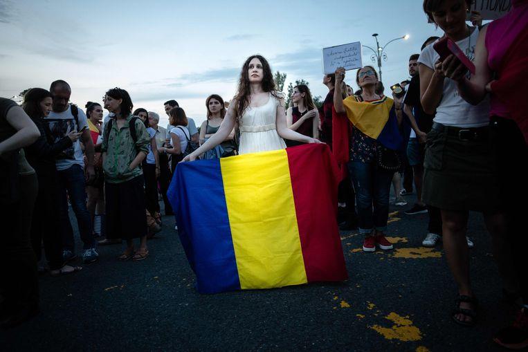Een vrouw houdt een Roemeense vlag vast tijdens een protest in Boekarest.  Beeld AFP