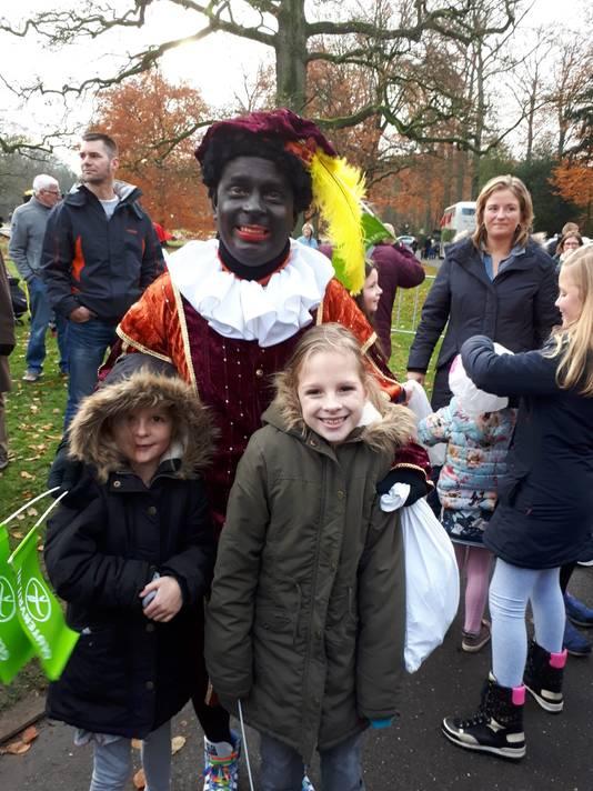 Glutenvrije Piet Winfred Coenraats met dochters Fleur (8, links) en Eva (10), die coeliakie heeft. De Glutenvrije Piet is herkenbaar aan een groen vlaggetje op zijn baret, waar 'Glutenvrij' op staat. Hij zwaait ook met groene vlaggetjes. Kinderen met coeliakie herkent hij aan een speciale kleurplaat die zij in hun hand of op hun muts hebben geplaatst.