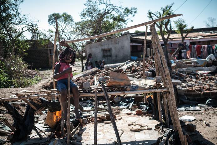 Een meisje zit op een marktkraampje dat de cycloon deels heeft doorstaan.