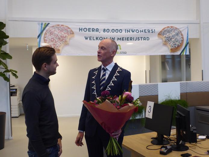 Sander den Houdijker neemt bloemen in ontvangst van burgemeester Marcel Fränzel. Sander is de papa van Evir, de 80.000ste inwoner van Meierijstad.
