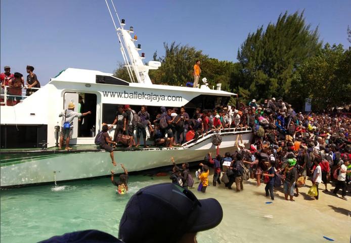 Toeristen proberen na de aardbeving in Lombok wanhopig een plekje op een boot te bemachtigen op het nabijgelegen eiland Gili Trawangan.