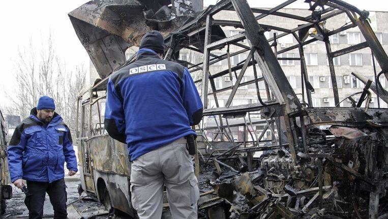 OVSE-waarnemers inspecteren bussen in Donetsk na een raketinslag op 11 februari. Beeld epa
