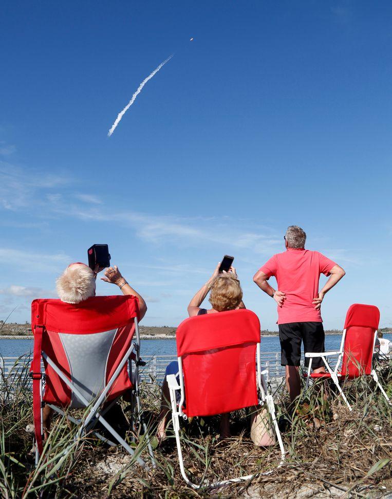 Toeschouwers bekijken de lancering van de Falcon Heavy.