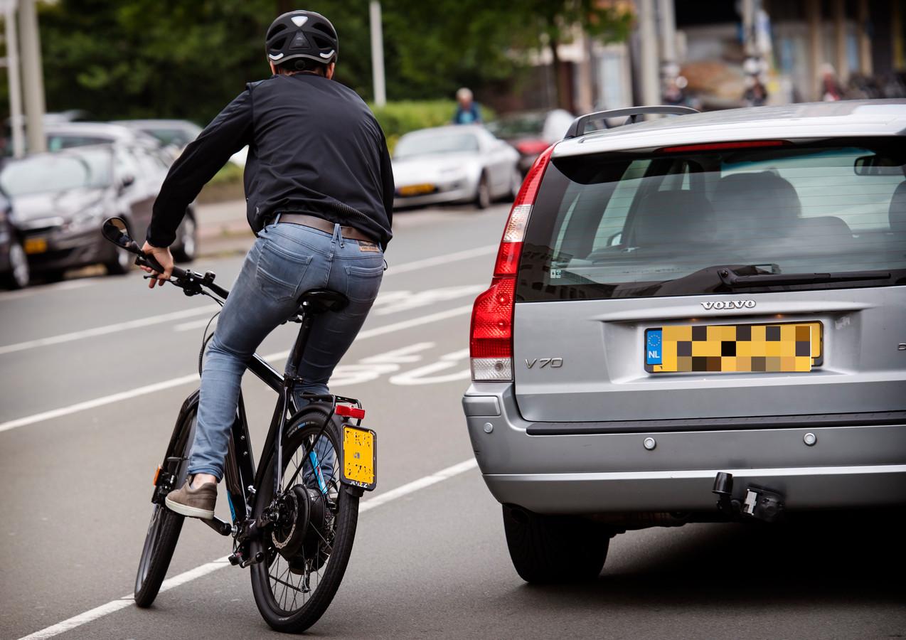Een speedpedelec, te herkennen aan de kentekenplaat en de achteruitkijkspiegel en de helm bij de bestuurder.