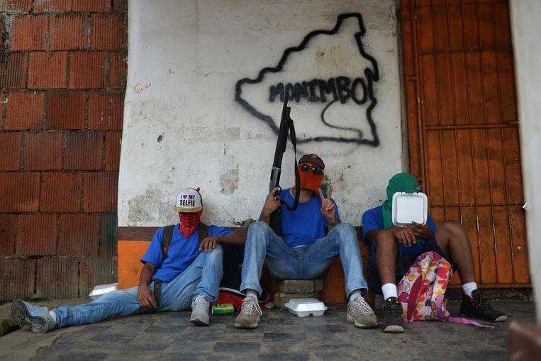 Paramilitairen rusten uit na confrontaties met demonstranten tegen Ortega. Beeld AFP