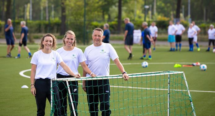 Buurtsportcoaches Meierijstad Jamie van Lankveld, Joyce van Bussel en Henry van Alebeek (vlnr) op het veld van Avanti in Schijndel. Op de achtergrond zijn senioren bezig met walking football.