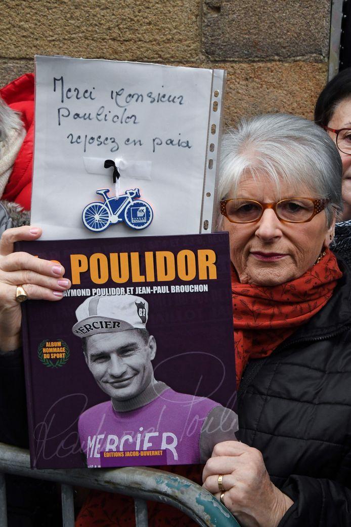Een vrouw houdt een foto van Raymond Poulidor omhoog met een tekst: 'Bedankt meneer Poulidor. Rust in vrede'.