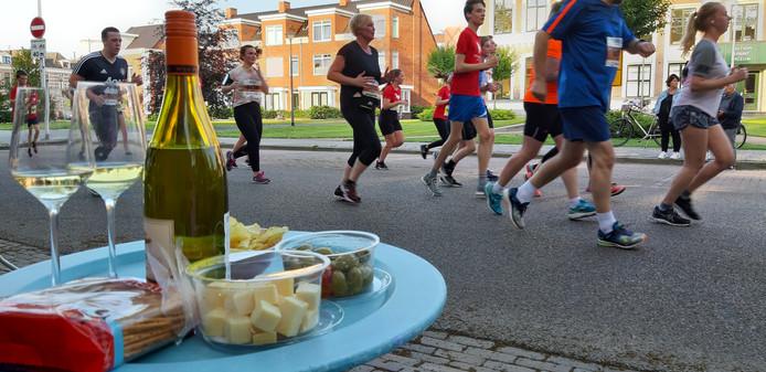 Deelnemers aan de vier Engelse mijlen, bewoners kijken toe vanaf de stoep met een hapje en een drankje.