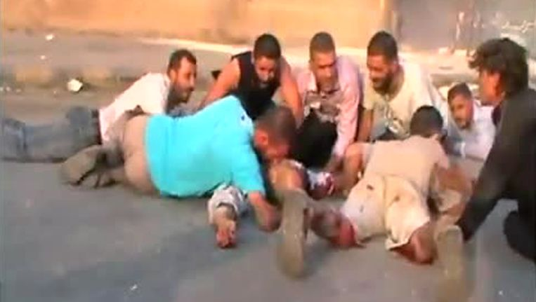 Beeld van een video op Youtube waarop Syriërs, volgens de maker, dekking zoeken voor beschietingen van het Syrische leger in Hama. Beeld AFP