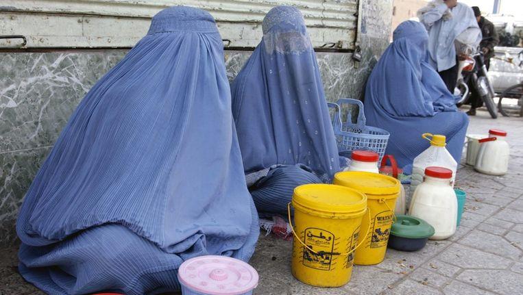 Afghaanse vrouwen verkopen goederen langs de weg in Herat. Beeld EPA
