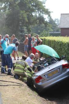 Cabrio rijdt greppel in, automobiliste bekneld