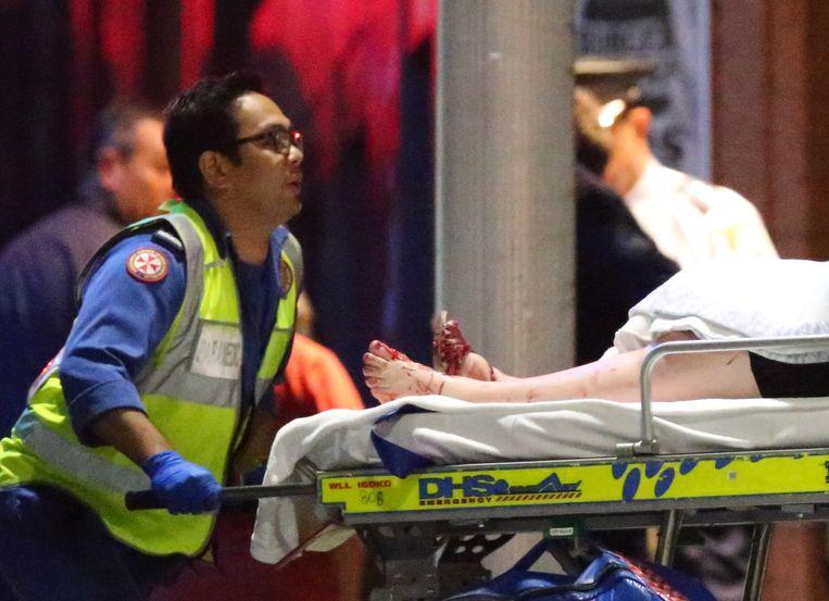 Een gewonde gegijzelde wordt naar een ambulance gebracht. Beeld ap