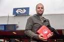 Nederland, Weesp Arnoud Vermeer op station Weesp met de AED die hij dankzij een actie met steun van oa de gemeente en vrienden & bekenden voor elkaar kreeg. Dit nadat hij tevergeefs een treinreiziger reanimeerde. Het apparaat hangt vlakbij het station