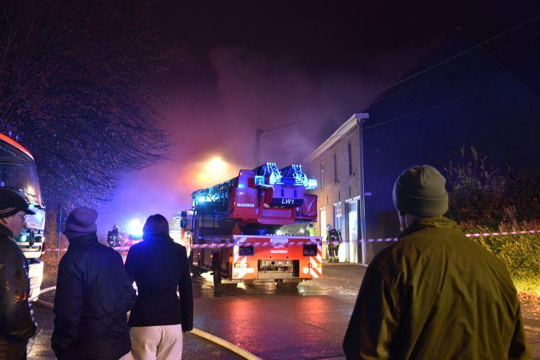 Terwijl het vuur hevig woedt, worden buurtbewoners op afstand gehouden.