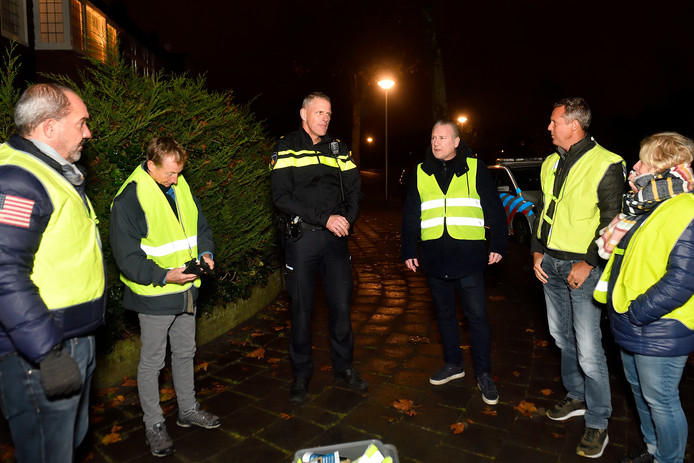 Frank van der Geest (links) en Ward Kentie (derde van rechts) luisteren met buurtgenoten naar de instructie van een agent.