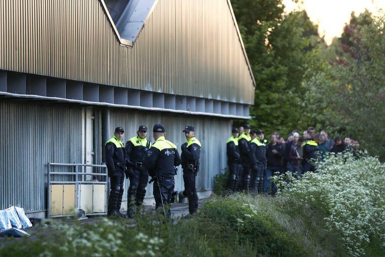 Politie in oproeruitrusting aan de stal waar de dierenrechtenactivisten zich hebben verschanst.