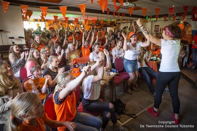 Tientallen handbalfans volgden in café Steggink het eerste handbalduel op de Spelen van de Oranjevouwen, met dorpsgenote Martine Smeets. Met haarband zus Annelies Smeets en met hoedje moeder Ans Smeets.