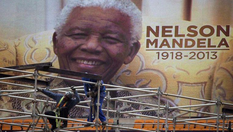 Een van de afbeeldingen van Nelson Mandela die aan de buitenzijde van het FNB-stadion in Johannesburg, ook wel bekend als Soccer City, worden bevestigd. Beeld reuters