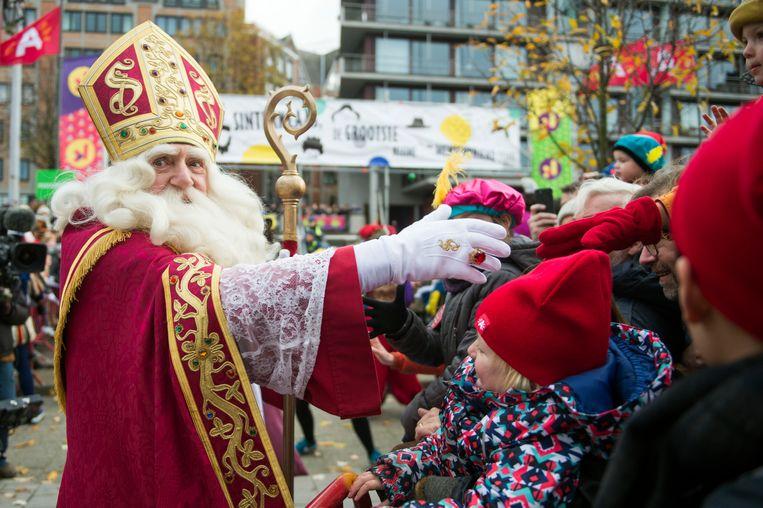 Sinterklaas begroet enkele enthousiaste kinderen in Antwerpen.