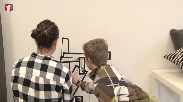 Twee kinderen tekenen op de muur van pop-up atelier Jan Doodle in Hengelo.